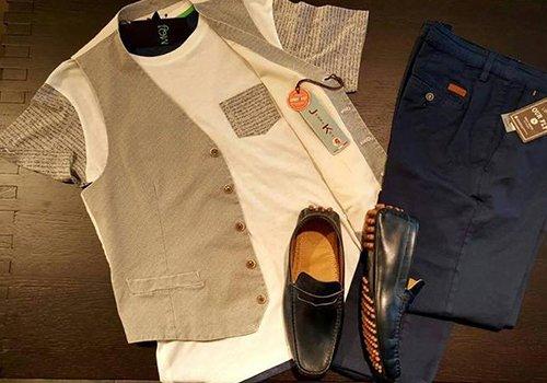 Pantalon blu marino, maglietta chiara, gilè marrone chiaro e scarpe neri