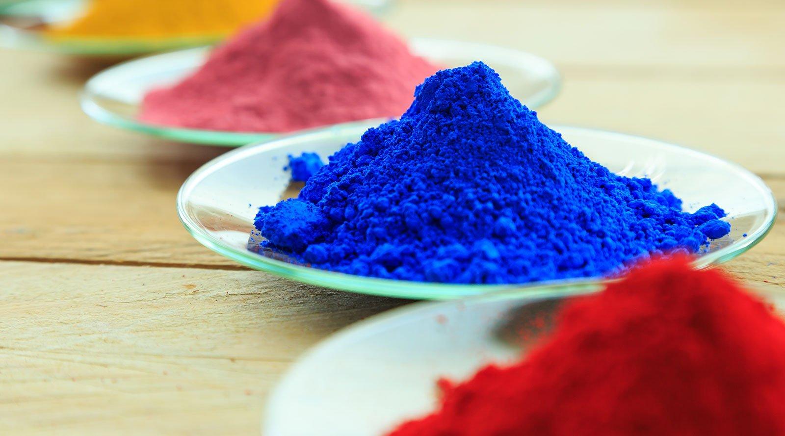 dei piatti con delle polveri blu,rosse,rosa e gialle