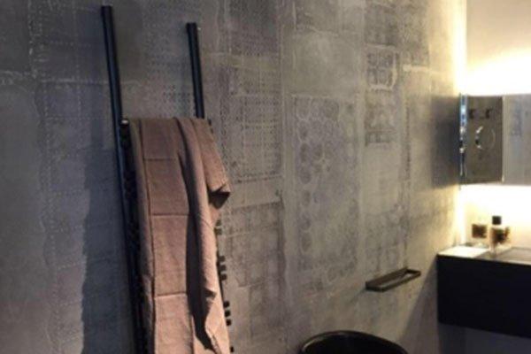 una parete di color grigio in un bagno con una scaletta nera con sopra un asciugamano e una sedia marrone