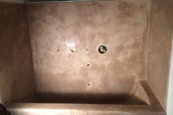vista di una vasca di un lavabo in marmo di color rosa e in mezzo il buco per il rubinetto