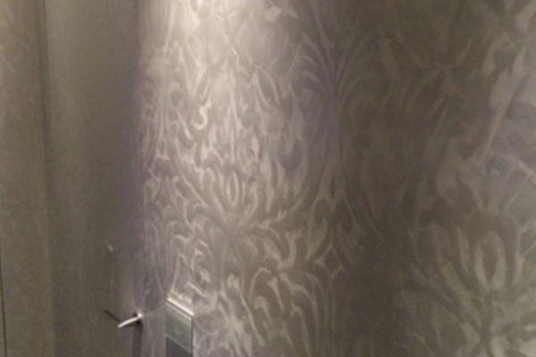 un muro con disegni a fiori bianchi  e sulla sinistra una maniglia di una porta