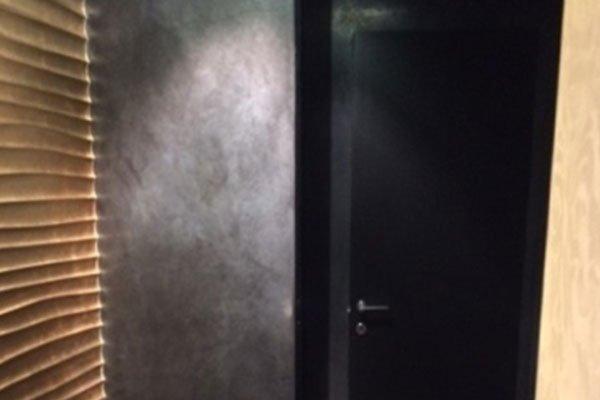 una stanza con muri neri, una porta nera e sulla sinistra una tenda marrone