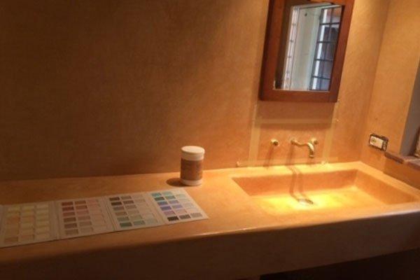 un lavabo bianco,un piano fatto di piastrelle verdi e sopra uno specchio da cui riflette l'immagine di una persiana marrone