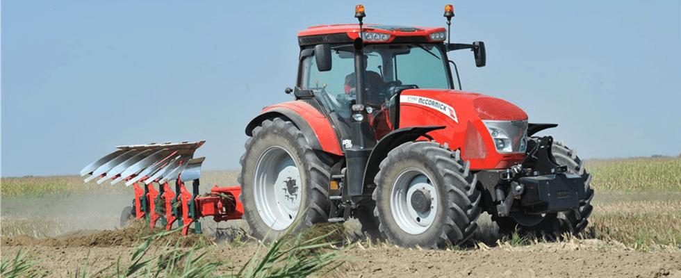 un trattore arancione in un campo agricolo
