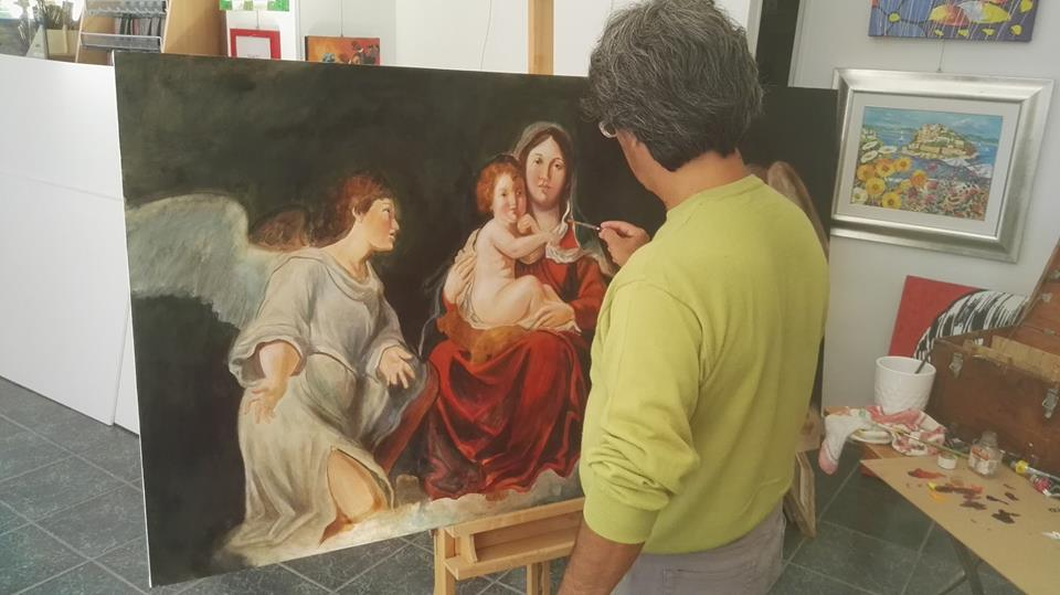 un artista mentre dipinge un quadro con un pennello in mano