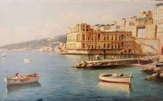 una cittadina marittima con vista delle barche nel mare e delle montagne in lontananza