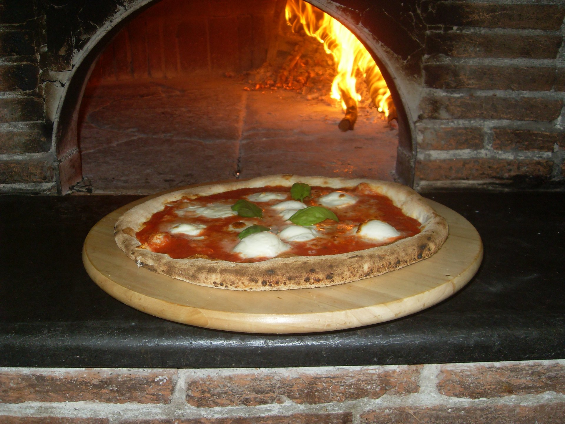 una pizza al lato di un forno a legna