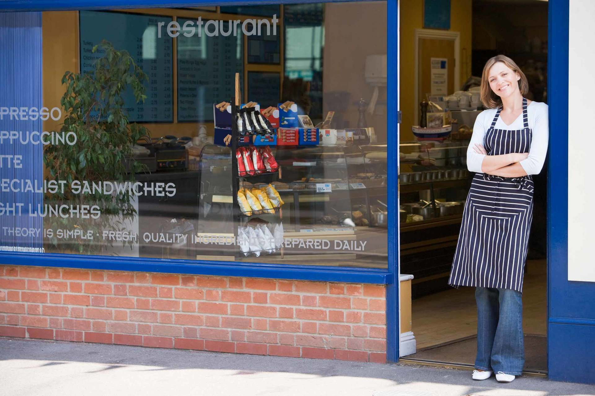 business owner standing by door of restaurant