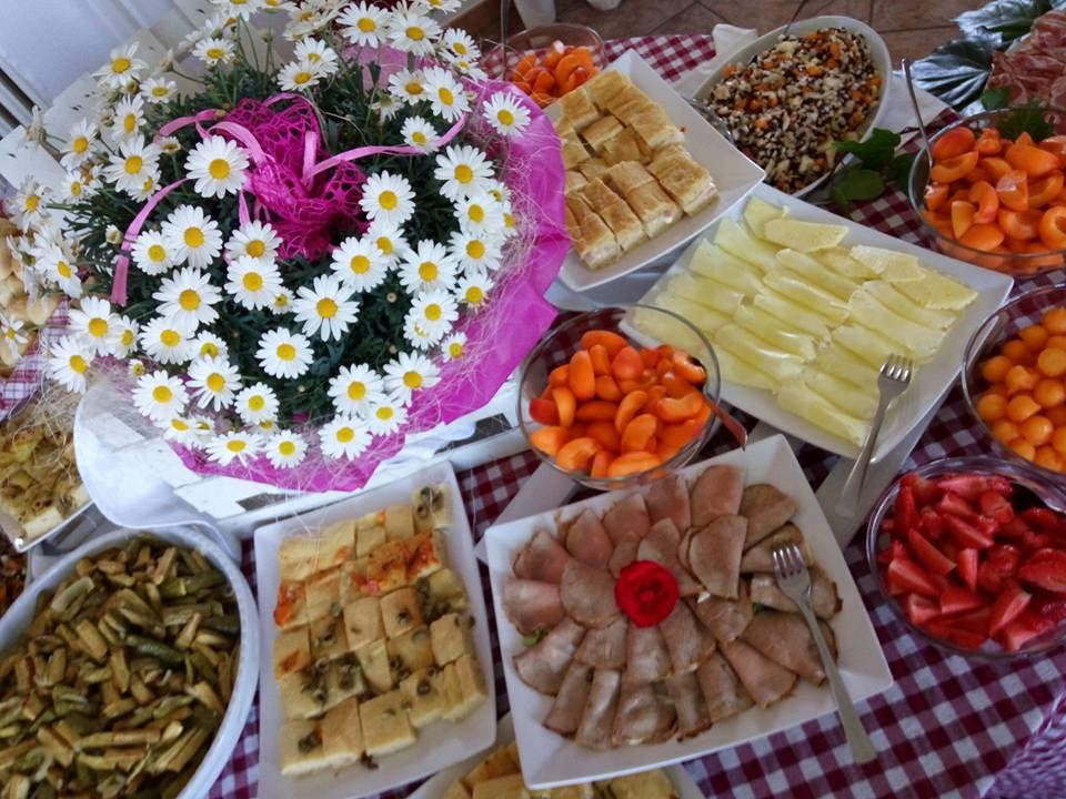 un buffet con roast beef, verdure e un bouquet di margherite