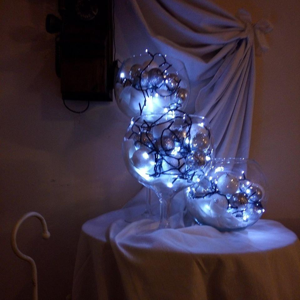 dei vasi di cristallo con delle palline illuminate all'interno