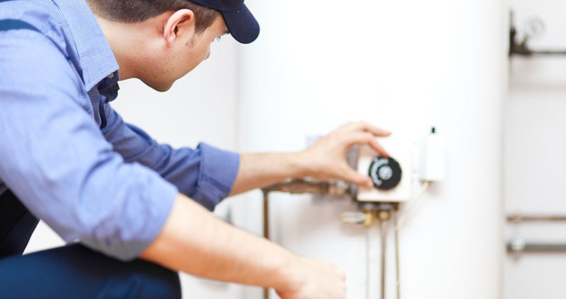 Repairman fixing the hot water heater in a customer's home