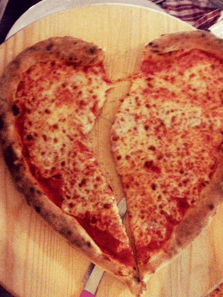 pizza margherita a forma di cuore tagliata a meta'