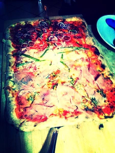 pizza rettangolare con salame, peperoni, cipolle e prosciutto cotto