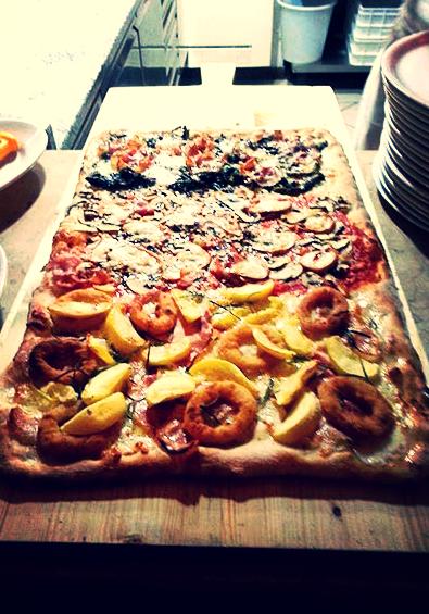 una pizza con anelli di  cipolla,patate, verdure, wurstel e prosciutto a forma rettangolare su un tagliere di legno
