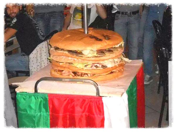 un carrello con una tovaglia in tema bandiera italiana con un tagliere e sopra un panino gigante con carne e verdure