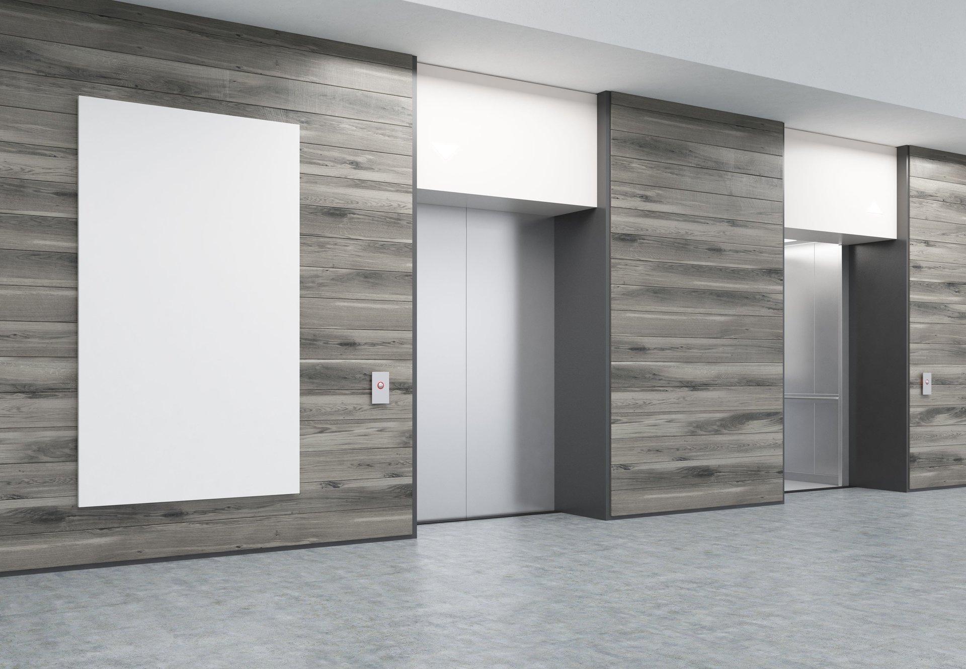Stanza con pavimento grigio e 2 ascensori