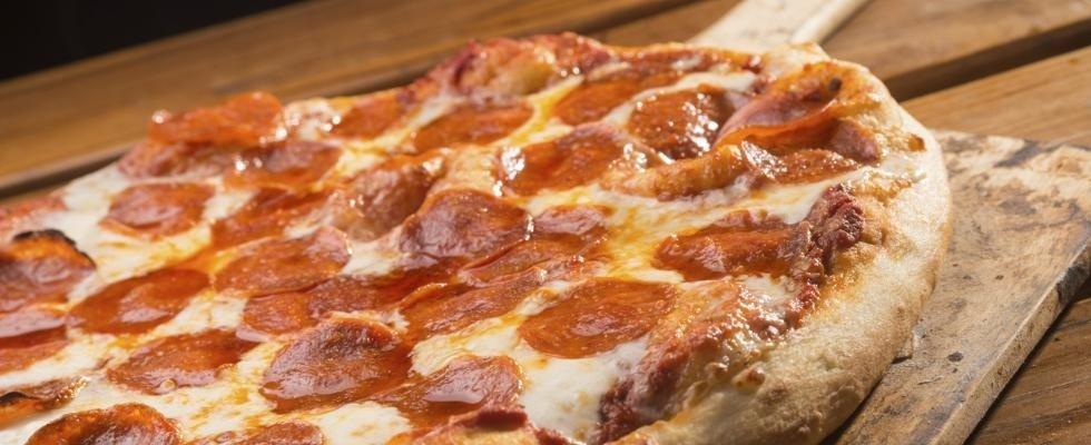 pizza al salame piccante su tagliere cotta in forno