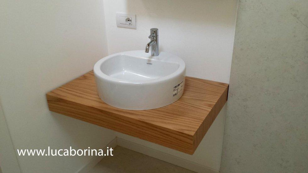 una mensola in legno con sopra un lavabo rotondo