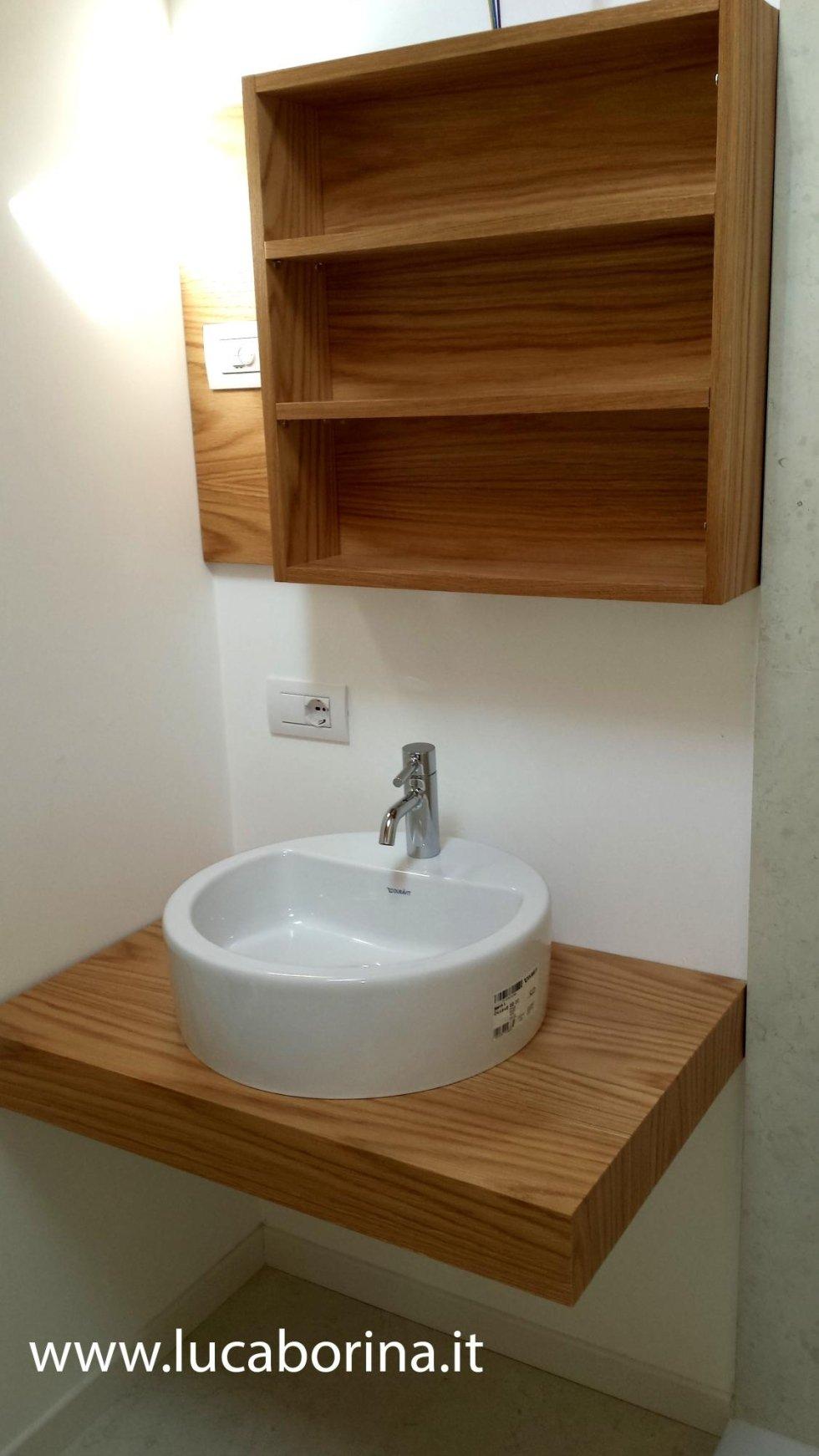 una mensola in legno con sopra un lavabo rotondo e delle mensole al muro