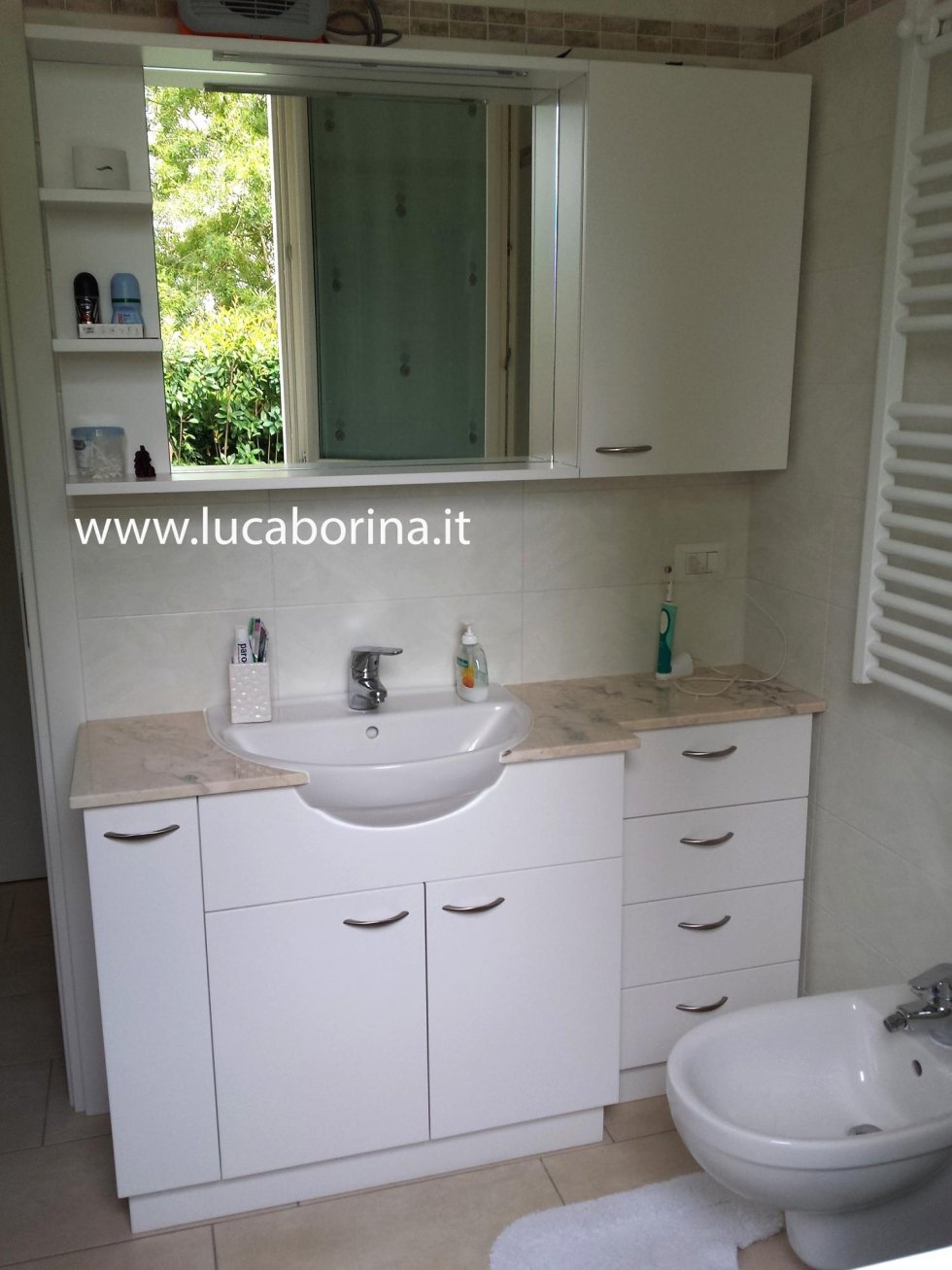 un mobile da lavabo di color bianco con dei cassetti e uno specchio