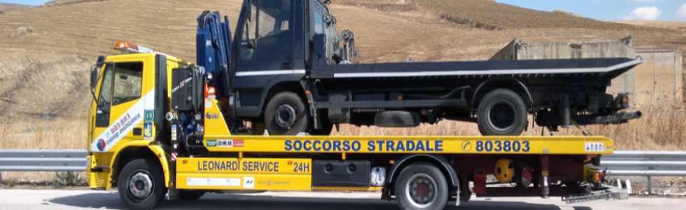 Autogru trasportando un camion blu