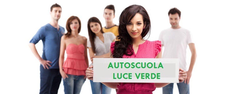 una ragazza con un cartellone bianca con scritto AUTOSCUOLA LUCE VERDE e in sfondo altri ragazzi