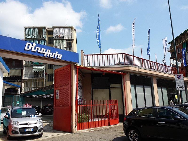 dino-torino-021 - esterno de3l concessionario con un cancello d'ingresso color rosso, insegna Dino Auto color bianca e blu e sotto una macchina Fiat 500 Abarth di color nero parcheggiata