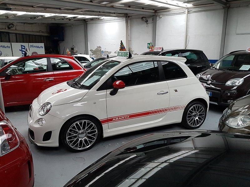 diverse vetture in vendita all'interno del concessionario, in risalto, una Fiat 500 Abarth di color bianco con rifiniture rosse
