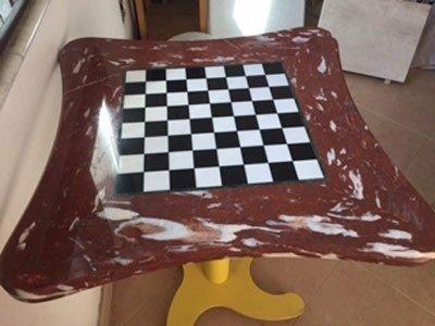 un tavolino in marmo bordeaux e a scacchi bianchi e neri