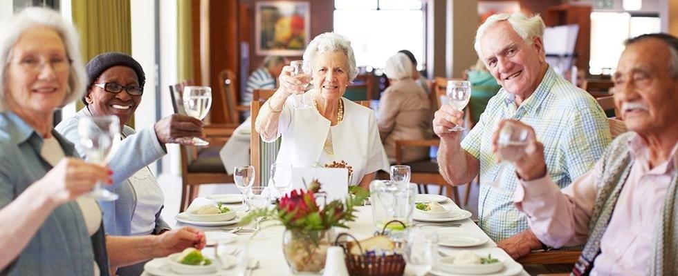 signori e signore anziane che brindano seduti a un tavolo