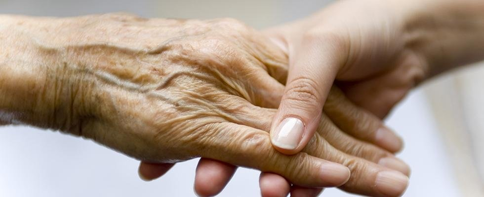 una mano di una ragazza che tiene quella di una persona anziana