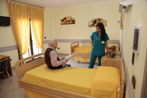 un'infermiera che parla con un signore seduto su un letto