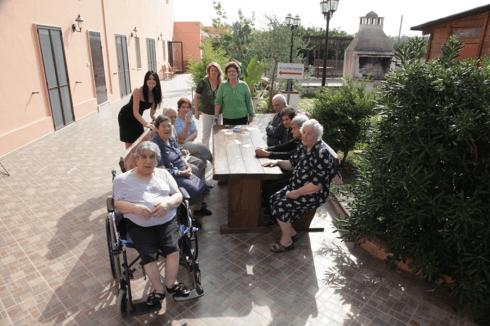 delle persone anziane sedute a un tavolo all'aperto