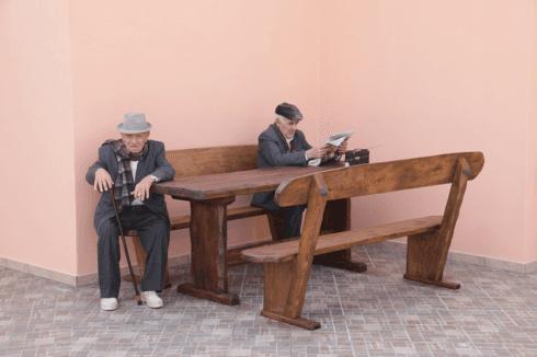 due signori anziani seduti su una panchina in legno vicino a un tavolo
