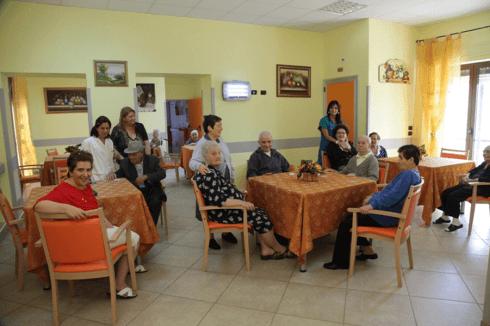 delle persone anziane sedute ai tavoli