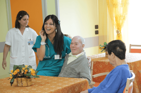 una signora e un signore anziano seduti al tavolo accanto una dottoressa