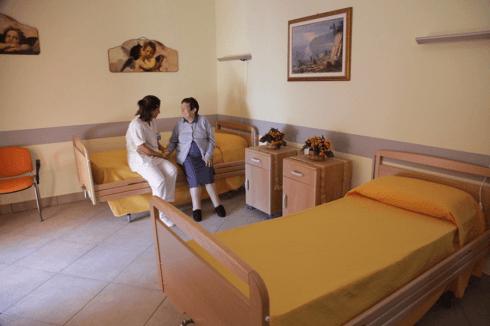 una stanza con due letti singoli e una signora anziana seduta accanto a una donna