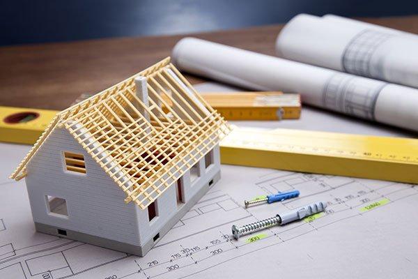 dei fogli con dei progetti,una livella e un modellino di una casa