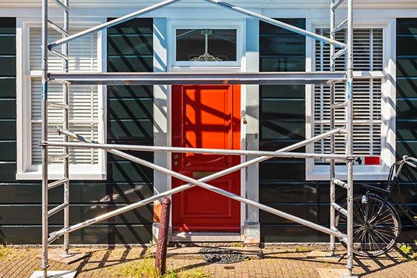un'impalcatura in metallo di fronte alla porta di una casa