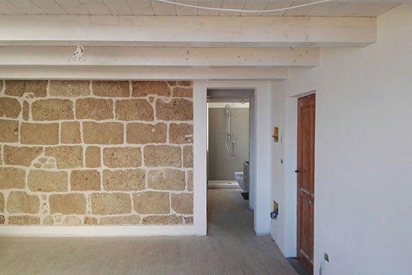 un muro in pietra in una casa e un corridoio con vista del bagno
