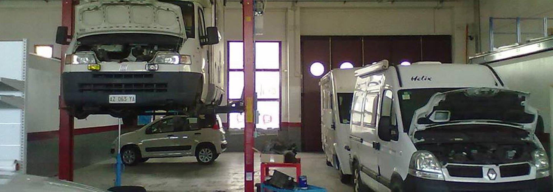 Interno dell'officina con furgoni, auto e camper in fase di riparazione