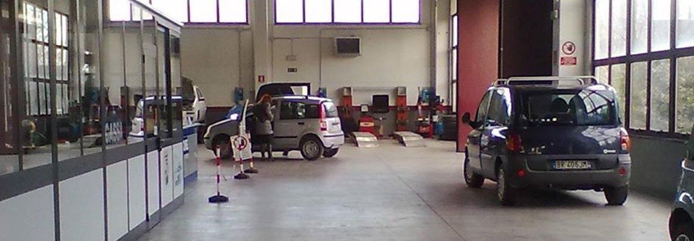 Interno dell'officina meccanica con delle auto Fiat parcheggiate