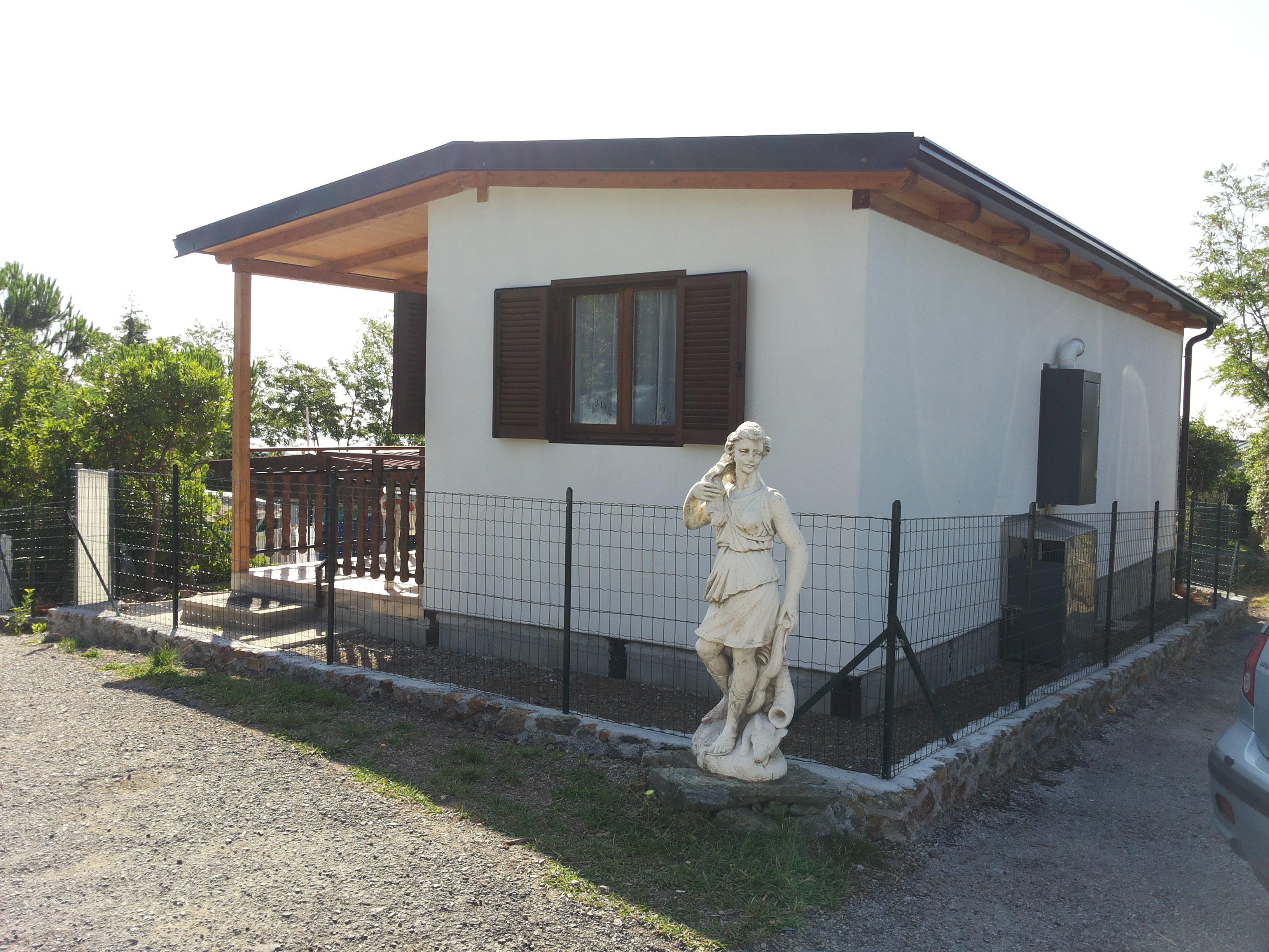 Bungalow di color bianco con statua di marmo all'esterno
