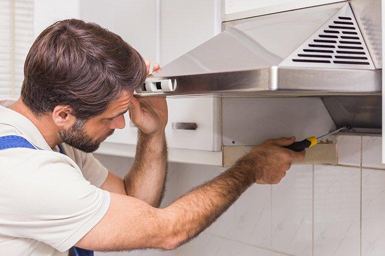 electrician repairing rangehood of stove