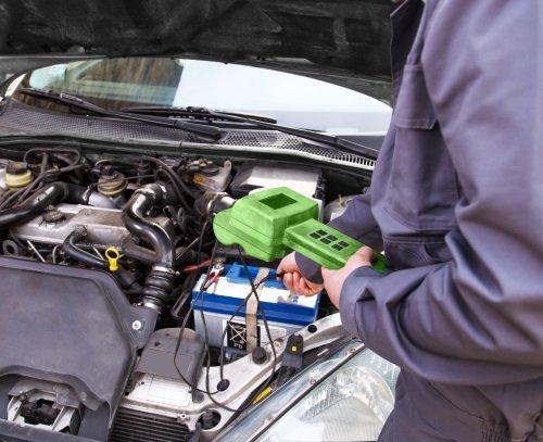 un meccanico con un apparecchio di diagnostica durante un test di una vettura