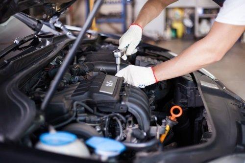 due mani con un attrezzo che svita un bullone della zona motore di una vettura