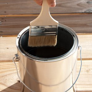 Paint brush going in a pot of black paint