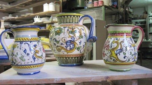 Dei vasi in ceramica di diversi colori con dei manici
