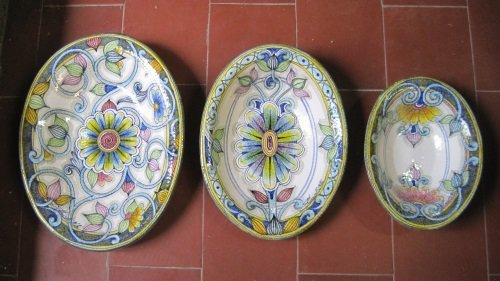 Dei piatti in ceramica con disegni a  fiori di color blu, bianco e giallo
