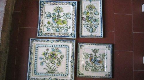 Dei piatti quadrati in ceramica con disegni a  fiori di color blu, bianco e giallo